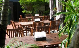 Outdoor tables and chairs surrounded by plants