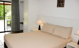 Inside Deluxe room with neatly made bed and beside lamps.