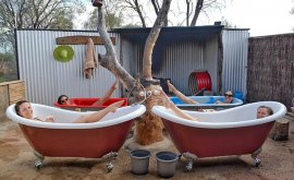 Girls lying in red claw foot bath tubs