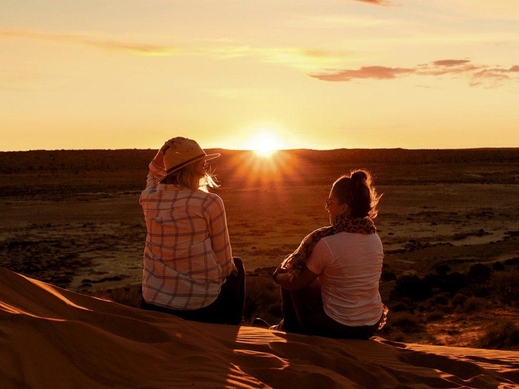 Women watching sunset on top of sand dune in Birdsville